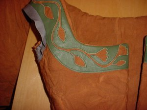 Reverse applique of flowers on a vine, done in leather.