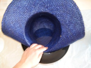 Gently introduce your hat to the bowl of warm water.  The straw will become more pliable as it becomes wet, and will start to lose shape.  You might have to turn it round and round in the bowl to get it evenly wet.
