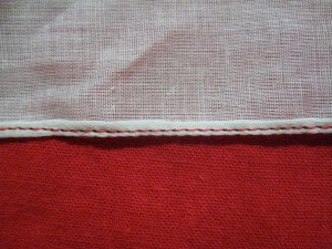 The rolled hem, seen from the wrong side of the fabric.