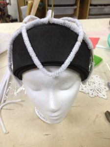 The next hanger is a wider football shape that stabilizes the headdress against the forehead and back of head.  The whole assembly is covered in white pipe cleaners.  (Has anyone ever cleaned a pipe with those?)
