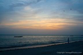 A man enjoying the evening settling over Atlantic ocean on the shores of Joal, Senegal. Photo by Marko Preslenkov.