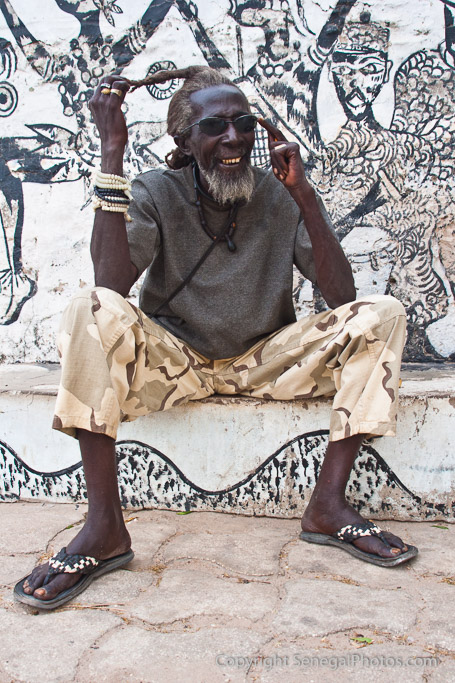 A local artist enjoying late afternoon chat with passers by in Joal, Senegal. Photo by Marko Preslenkov.