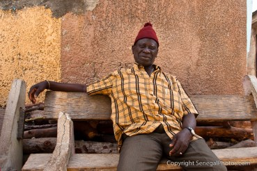 A man with a red hat enjoying the hot afternoon sitting on a wooden bench in Fadiout, Senegal. Photo by Marko Preslenkov.