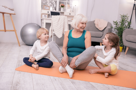 happy woman exercising with grandchildren