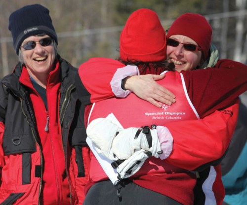 Chantal hugs an athlete after the snowshoe event.