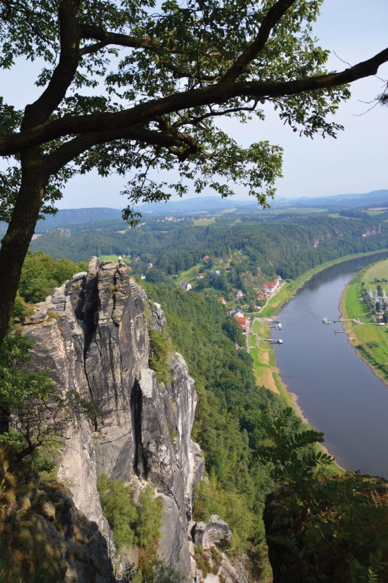 Saxon Switzerland terrace view of the Elbe River, villages and sandstone spires.