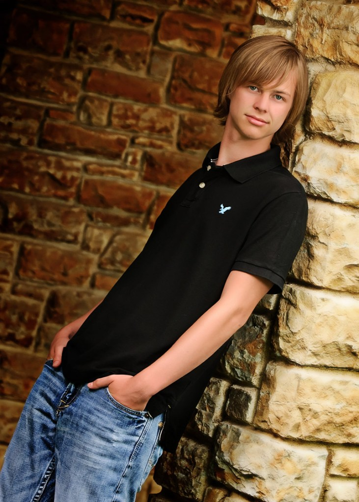 Photo pose of a high school senior boy leaning against a stone wall with his hands in his pockets