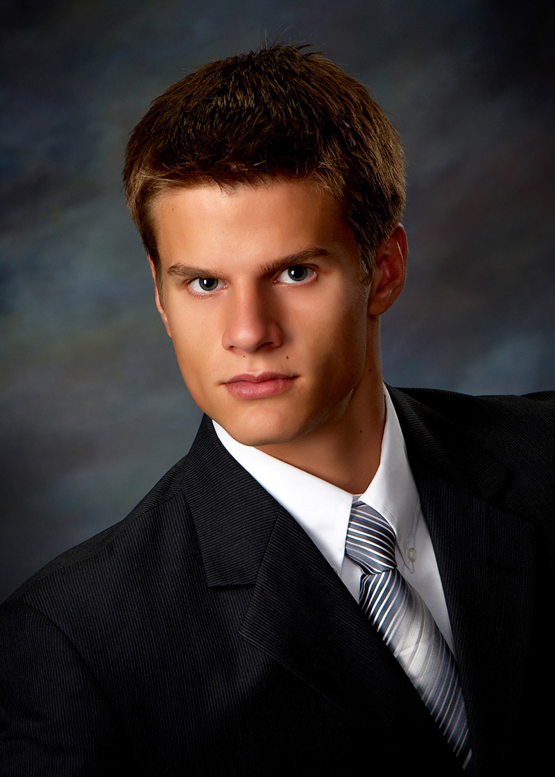 High school boy posed for his formal senior portraits wearing a suit and tie and a serious expression