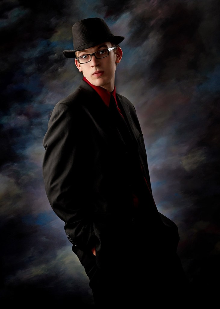 Classic formal senior portraits should also portray the subject's personality like this image of boy wearing a hat and hands in his pockets