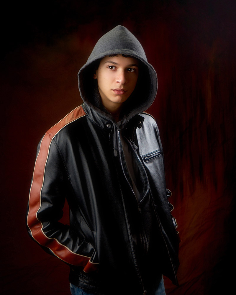 Standing pose for senior pictures for guys in studio with hooded sweatshirt