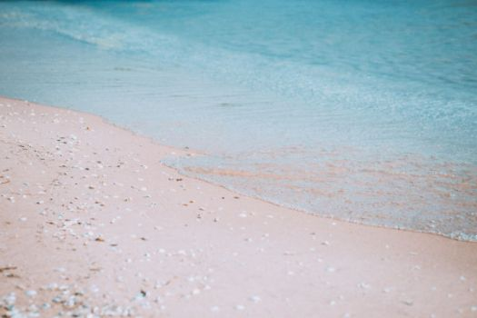 calm seashore with sand and aqua water