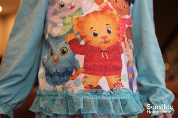 toddler's torso with aqua girl's Daniel Tiger PJ shirt