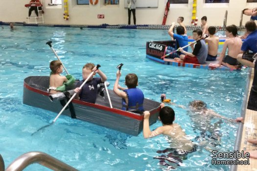 Boys racing DIY cardboard and duct tape boats in indoor YMCA pool
