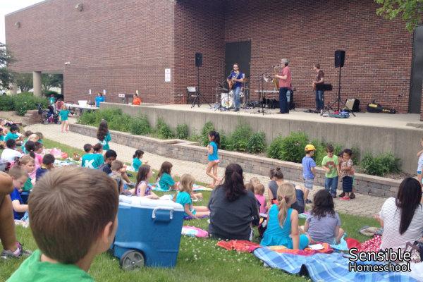 Families watching singers at outdoor kids' concert