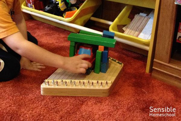 boy playing toy truck in wooden block garage on toy harp