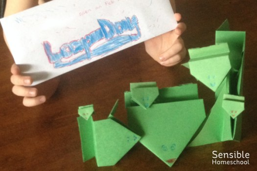 Boy holding leap day letter pictured with green paper leaping frog craft