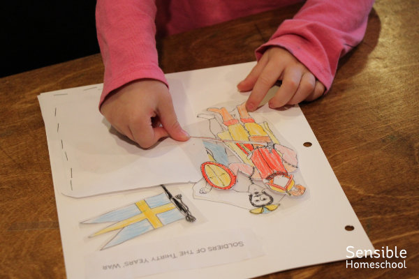 Preschooler playing with soldier paper dolls and their uniforms.