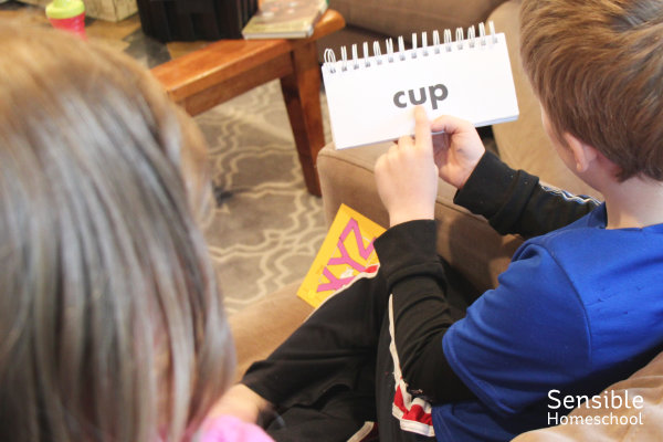 2nd grade homeschooler helping preschooler sound out words in phonics flip book.