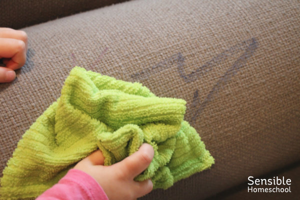 Preschooler cleaning up marker marks on sofa