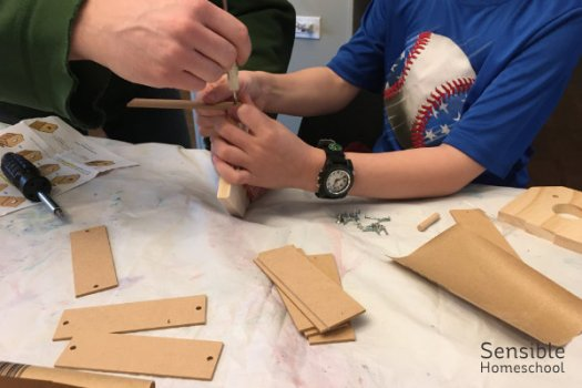 2nd grade homeschooler building a birdhouse at the dining table