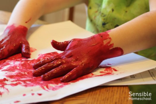 Preschool homeschool boy (with hands covered in red paint) painting at dining table.