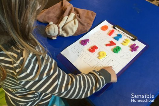 Preschool homeschool girl working on math at child's folding table.