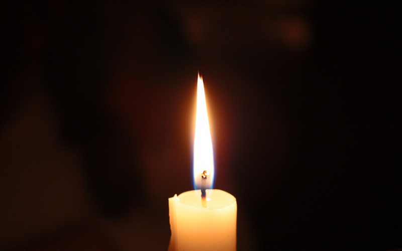 Single lit memorial candle on black background