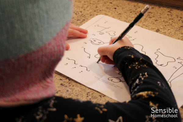 Preschooler writing on a dot-to-dot puzzle page