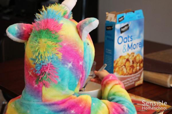 Preschooler in rainbow robe eating cereal