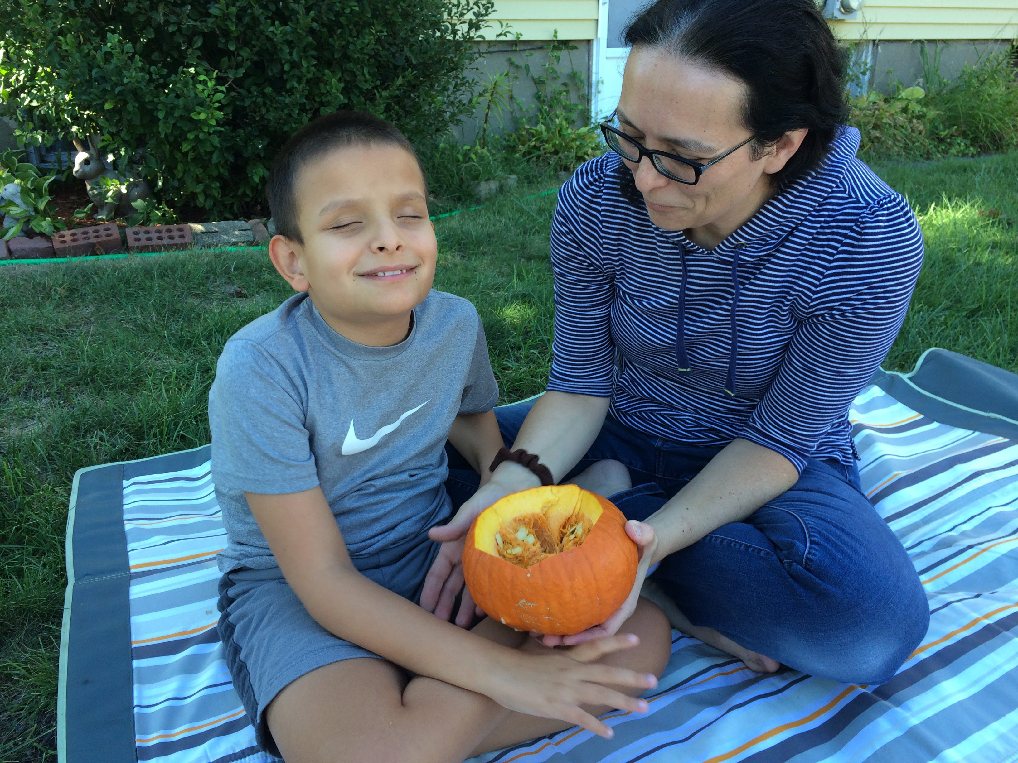 smiling boy holding a pumpkin cut open