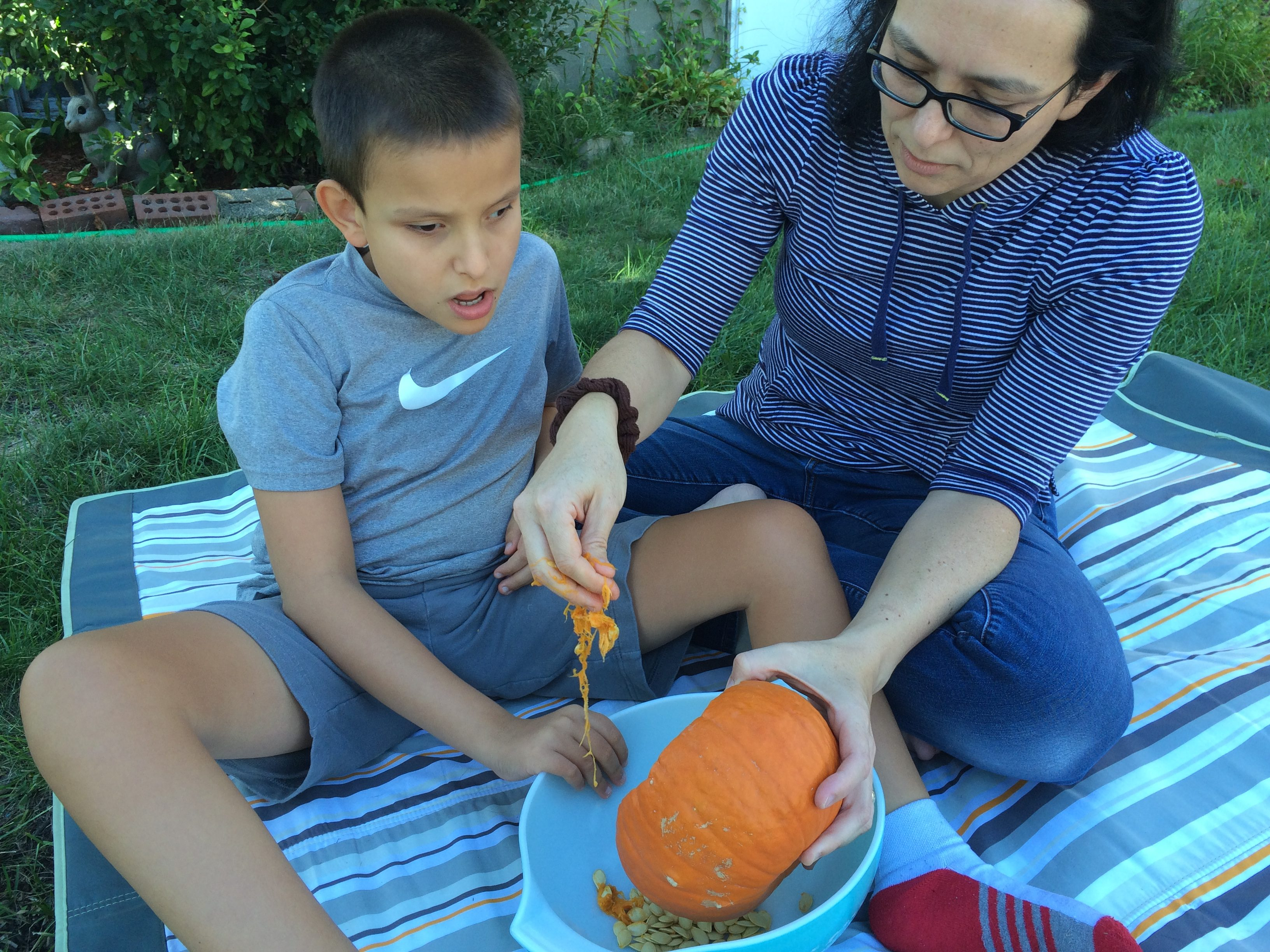 boy and mom scoop the goop out of the pumpkin
