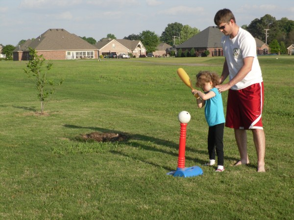 Little girl with dad hitting ball off tee