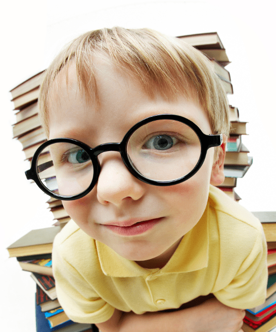 boy with glasses sitting in front of a pile of books