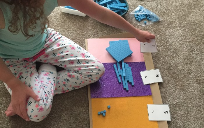 little girl using tactile graphical organizer with base ten blocks and braille numbers cards