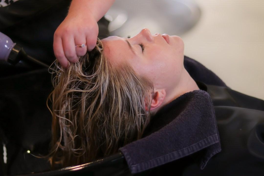 Blond dame som lener hodet tilbake i en frisørvask og får en deilig vask