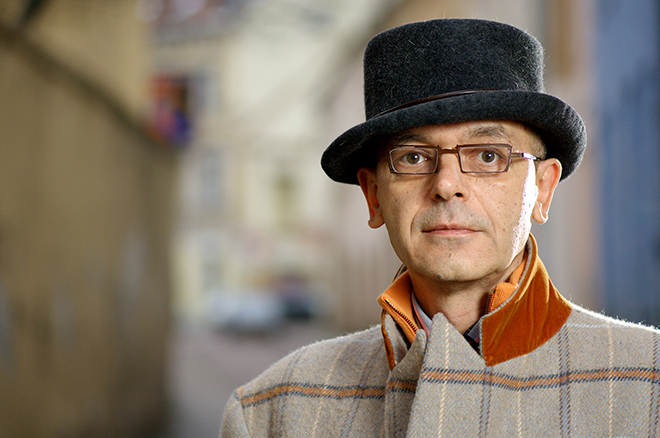 Photographic portrait of jewelry designer Alex Šepkus, in top hat and traditional Lithuanian coat.