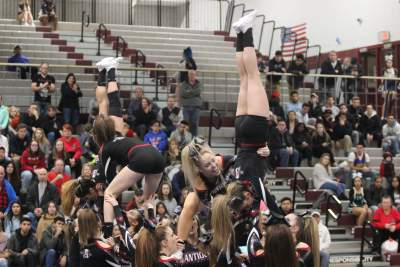 Cheer flipping their way to victory in cheerleading showing off their bows.