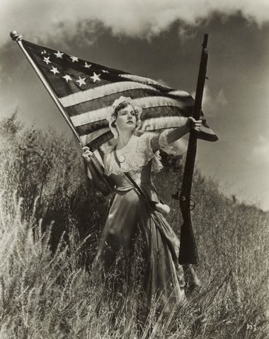 Madge Evans posing as Maxine Bennett from the film Age of Indiscretion. She is holding one of the earliest American flags with the stars in a circular pattern. And, of course, bearing a weapon. In those days, the right to bear arms was a common sense norm in America and Hollywood.