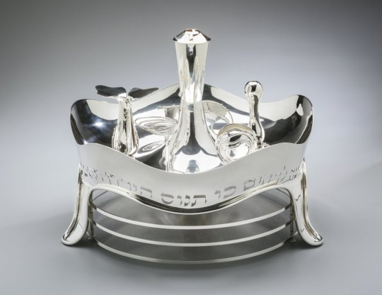 Three-tiered Seder plate Moshe Zabari, Israeli, b. 1935 New York, New York, United States, 1984 Silver: fabricated, spun, hammered, embossed, welded, and forged; formed wire; lucite tiers Overall: 14 1/2 × 18 1/4 in. (36.8 × 46.4 cm)