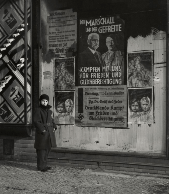 """Roman Vishniac Vishniac's Daughter Mara in Front of an Election Poster for Hindenburg and Hitler that reads """"The Marshal and the Corporal: Fight with Us for Peace and Equal Rights,"""" Wilmersdorf, Berlin, 1933 """"Fight with Us for Peace and Equal Rights"""" This sounds like the Democrat party whose obsession with equality is, in essence, the road to fascism."""