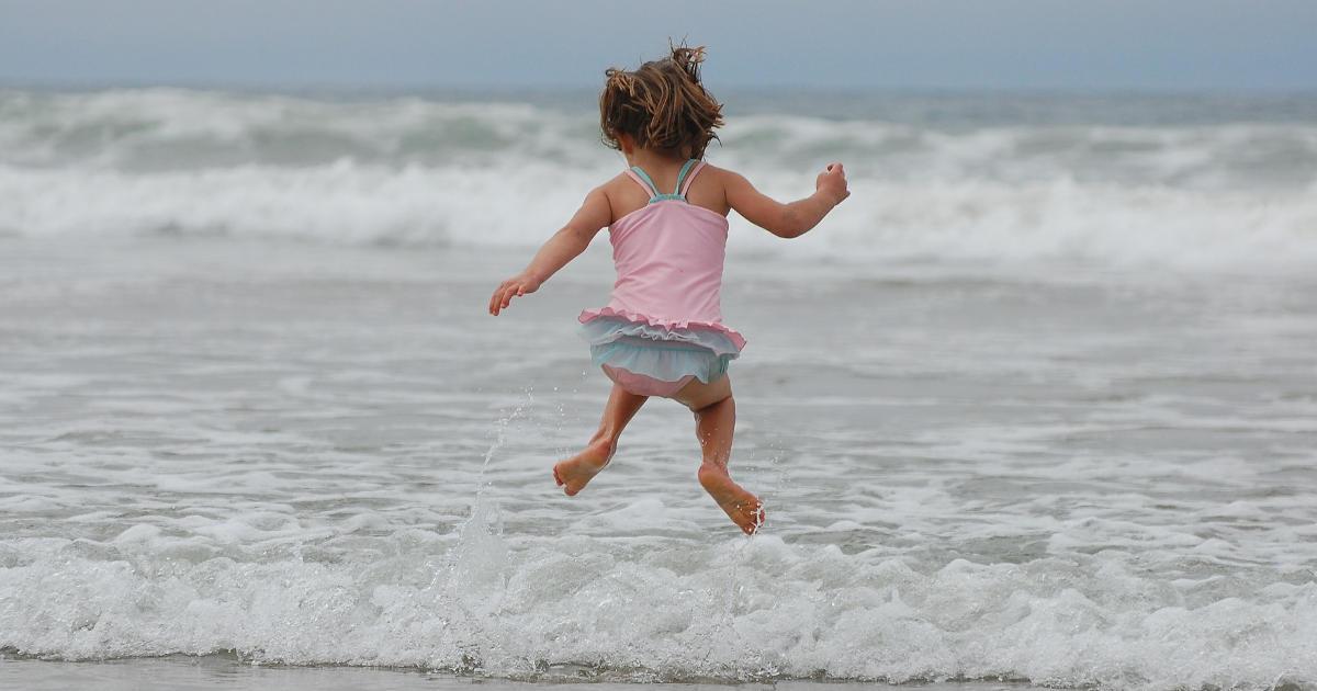 bambina che salta le onde del mare