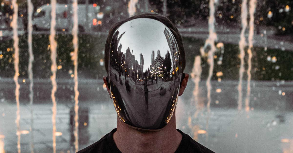 Una persona che indossa una maschera riflettente come uno specchio.