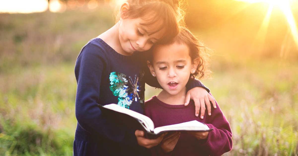 Due bambine che leggono un libro