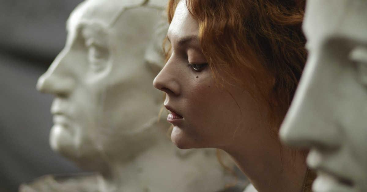 Un volto di donna fra facce di statue