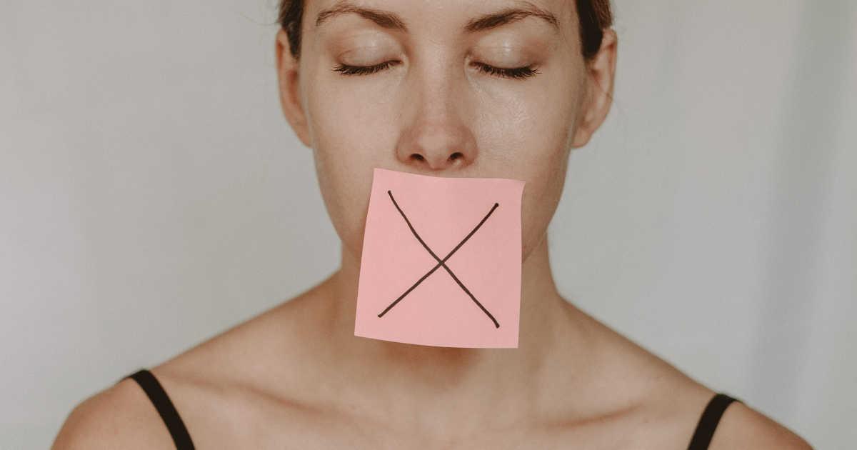 Una donna con un Post-It sulla bocca