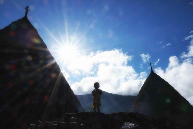 Seorang bocah di depan rumah adat di desa Wae Rebo