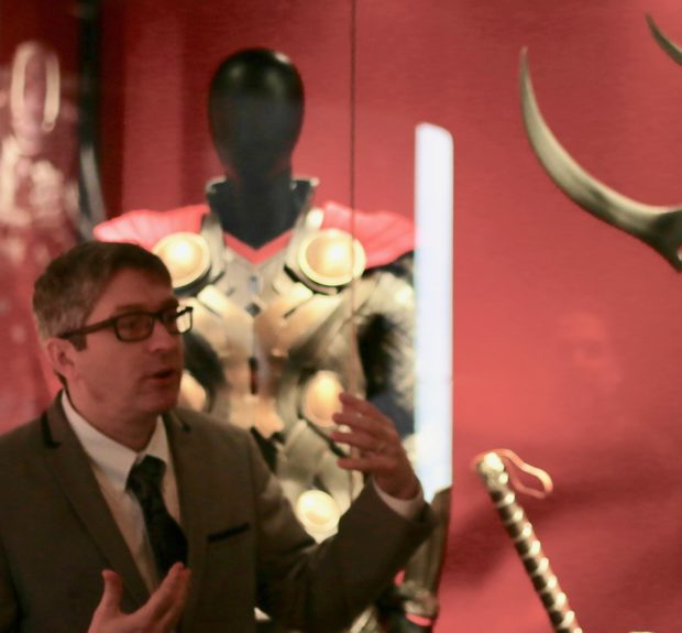 Saunders explains the origins of the exhibition as he stands in front of props from various Thor movies. Photo credit: Alyssa Rasmus/Pink Camera Media.