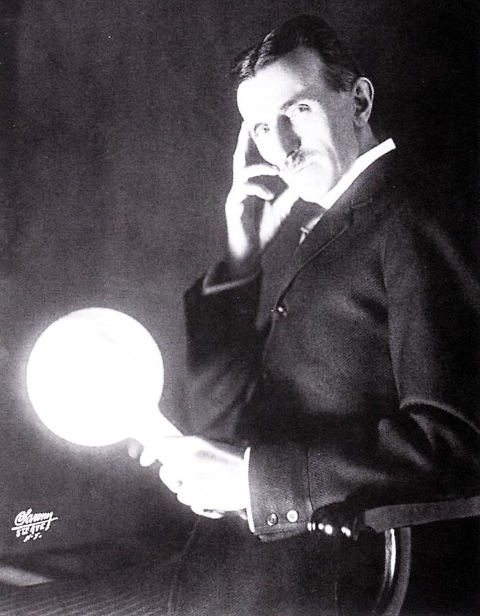 Imagem de Nikola Tesla segurando sua lâmpada de descarga ou fluorescente