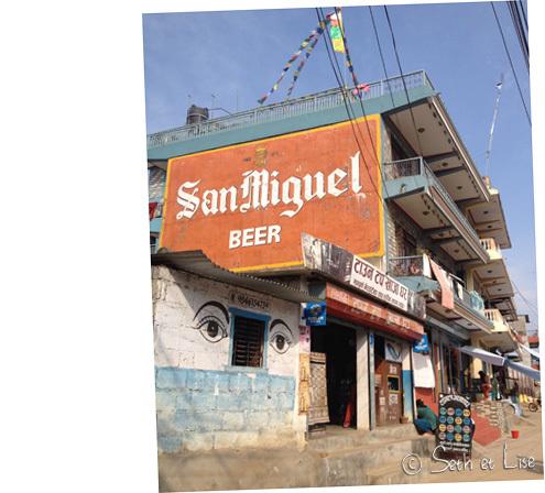 Le contraste des cultures. Les yeux de bouddha et les drapeaux de prière qui prennent en sandwich une pub pour une marque de bière.