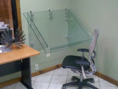 A custom glass drafting table with stylized hardware